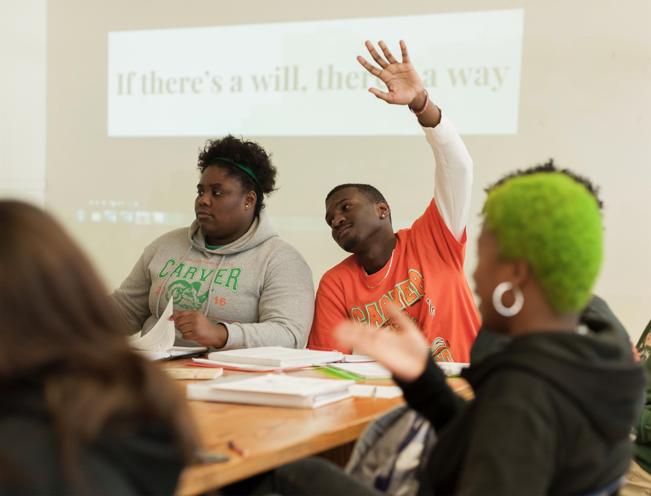 Photo of student raising hand in class
